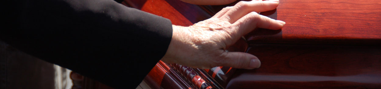 Picture of a grieving spouse with a hand on the casket